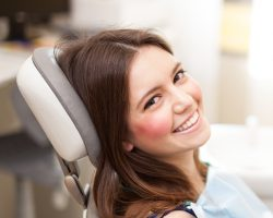 Women patient in dental chair smiling after her dental implant procedure at Malmquist Oral and Maxillofacial Surgery in Portland, OR