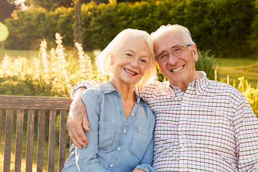 Elderly couple smiling on bench about their implant supported dentures at Malmquist Oral and Maxillofacial Surgery in Portland, OR