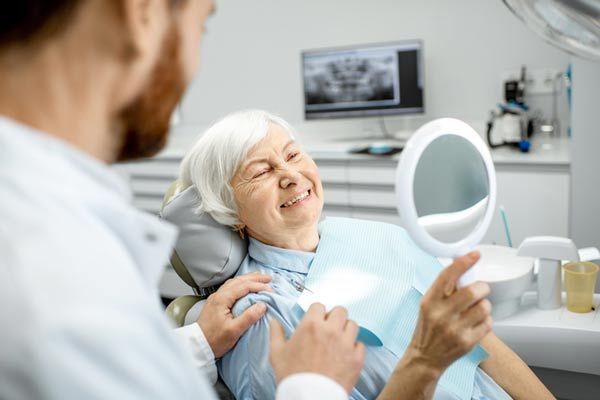 Elderly woman enjoying her implant supported dentures from Malmquist Oral and Maxillofacial Surgery in Portland, OR.