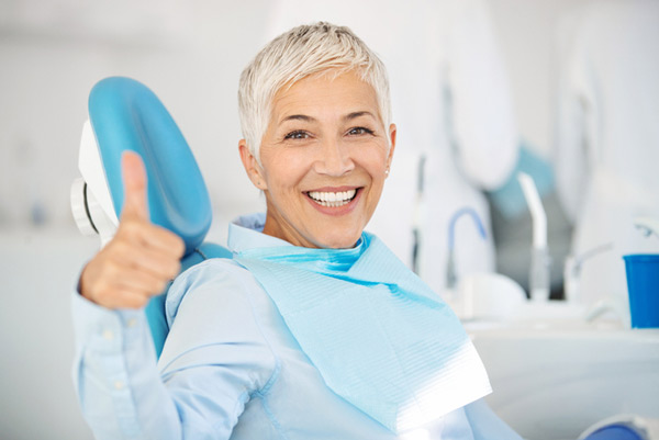 Mature woman smiling in a dental chair showing a thumbs up